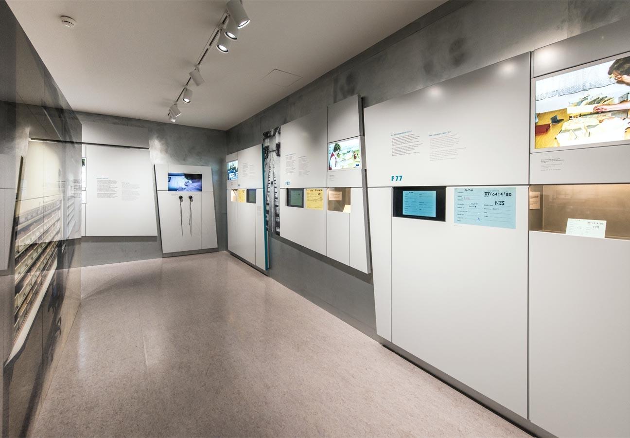 Ausstellungswände mit Medienstationen, Leuchtbildern und Vitrinen